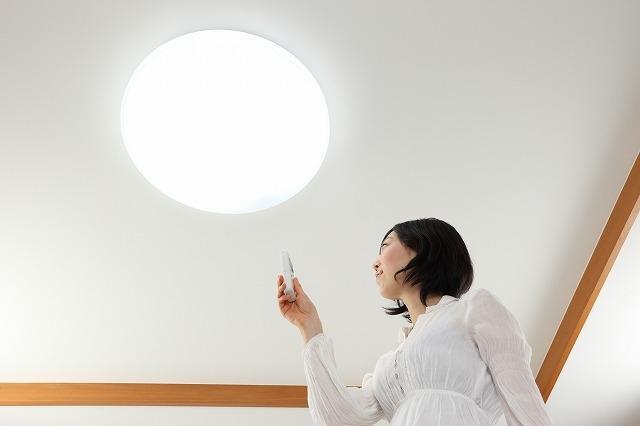 電気代節約のために照明を切ろうとしている女性の画像