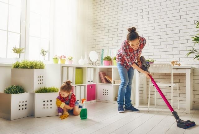 掃除機をかけている女性と子供