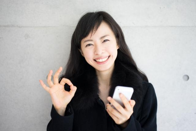 笑顔で電卓を持つ女性