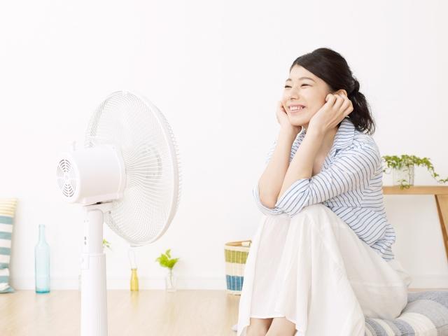 扇風機で涼む女性